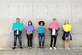 Group of young adults outdoors holding empty placard copy-space thought bubbles