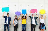 Group of young adults outdoors holding empty placard copyspace thought bubbles
