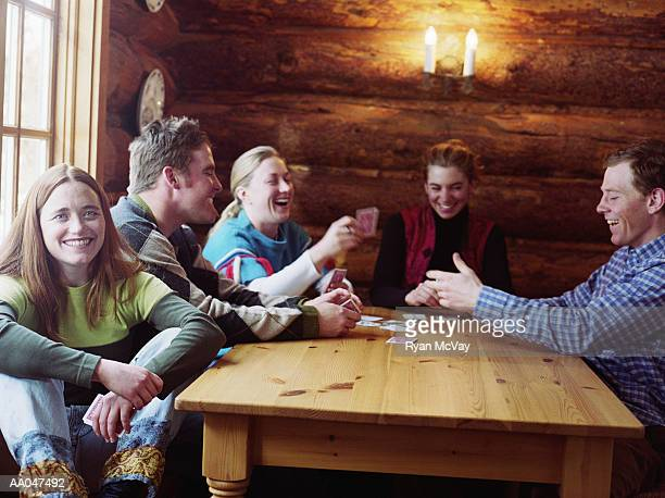 Group of young adults playing cards in log cabin, laughing
