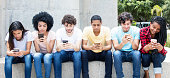 Group of young adults playing online game with phone outdoor in the summer