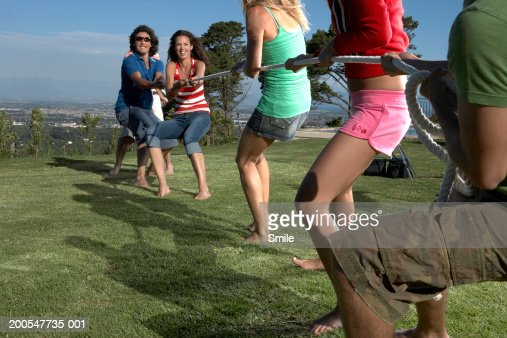 'Group of young adults playing tug of war in field, rear view' : Stock Photo
