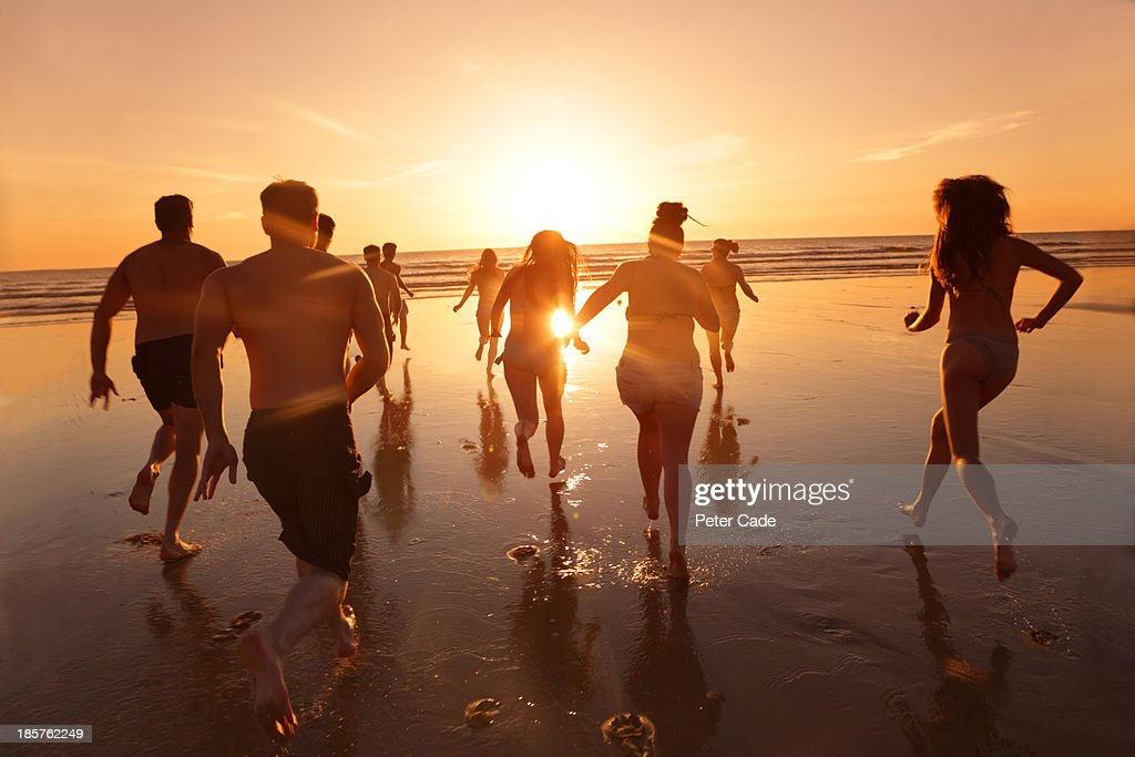 Group of young adults running into sea at sunset : Stock Photo