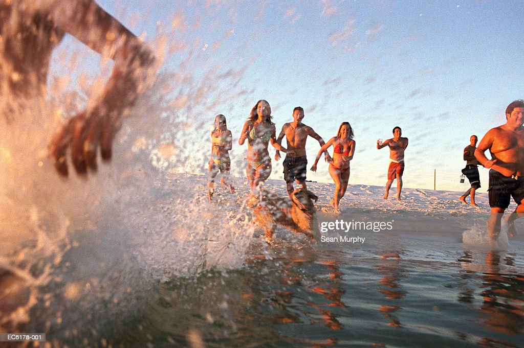Group of young adults running through water at ocean's shore : Stock Photo