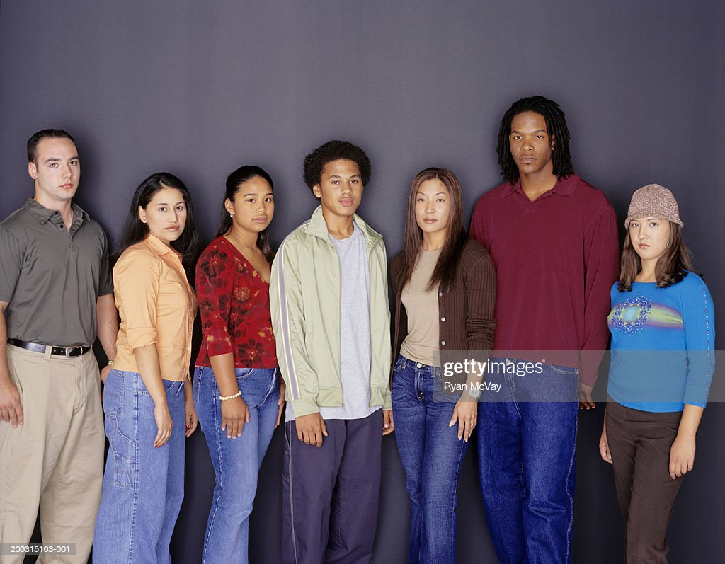 Group of young adults standing side by side, posing in studio, portrait : Stock Photo