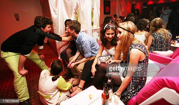 Group of young adults talking and drinking female in long velvet black gloves leaning on male with pastel green trousers 18th Birthday Party Nobu...