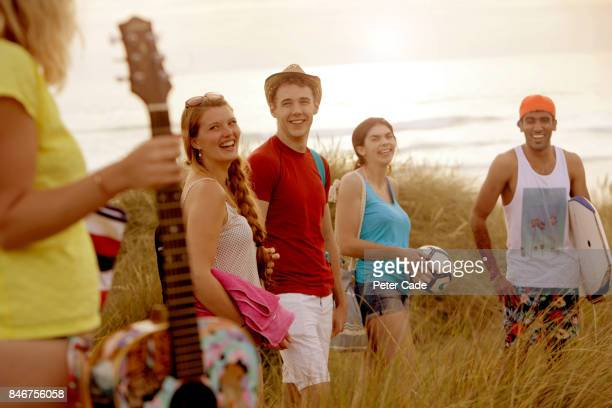 Group of young adults walking to beach at sunset for party