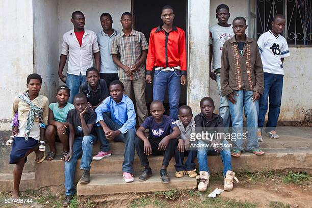 A group of young African boys sit and stand outside their care home run by Independent Christ International Christian Church in Chimoio Manica...