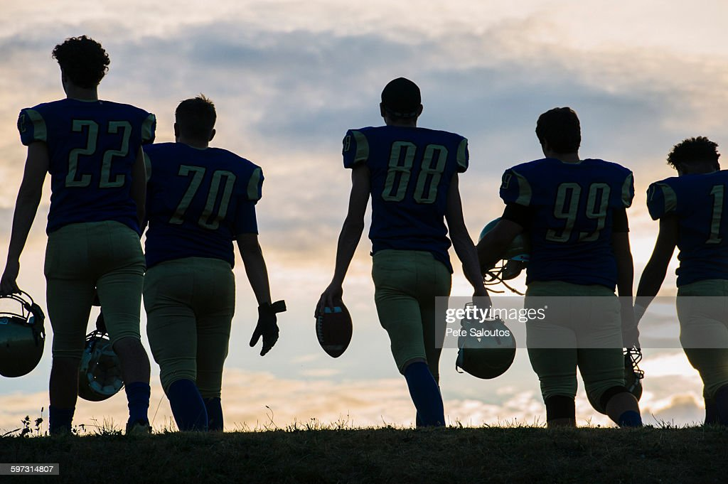 Group of young american football players walking away, rear view