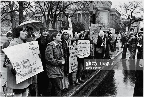 A group of young American women protest in the rain for women's rights as police look on along the street near a government building during Richard...