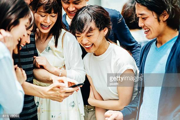 のグループ若いアジア人の友人にスマートフォン
