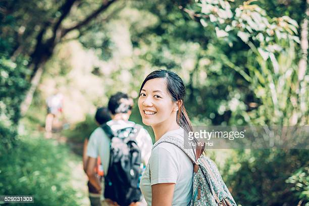 Group of young backpackers walking along in forest