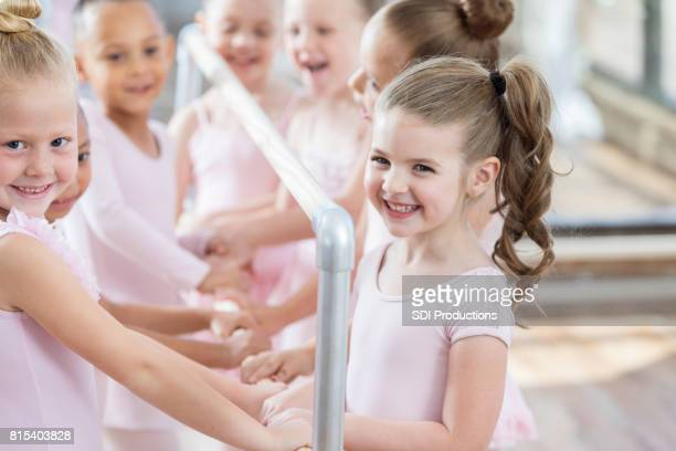 A group of young ballerinas smile while holding ballet barre