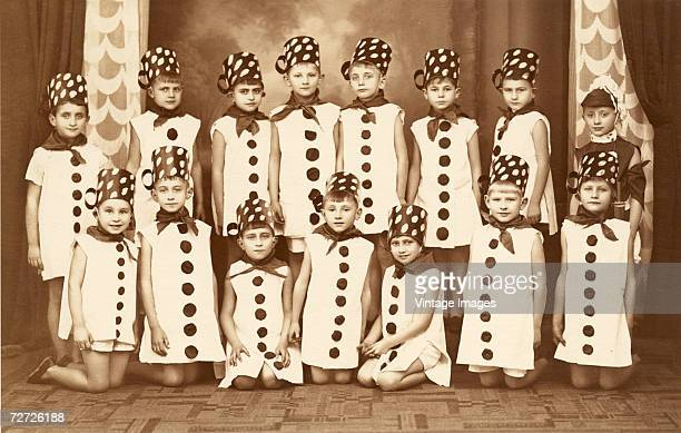 A group of young boys and girls poses for a picture on stage in their polkadotted sleeveless frock costumes for some sort of theatrical production...