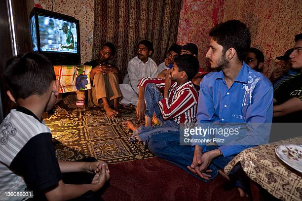 A group of young boys and men in Lahore Pakistan watching Pakistan and the West Indies play their quarterfinal match at the 2011 Cricket World Cup...