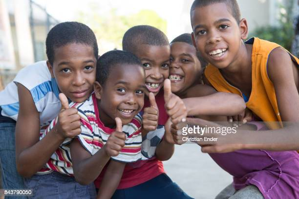 Santa Domingo Dominican Republic November 30 2012 A group of young boys are smiling and giving their thumbs up towards the camera in the poor...