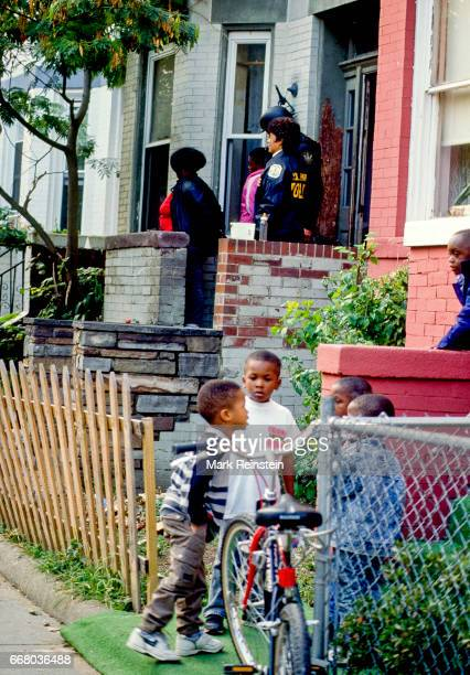 A group of young boys talk amongst themselves as next door US Park police officers arrest people in a suspected crack house Washington DC 1990