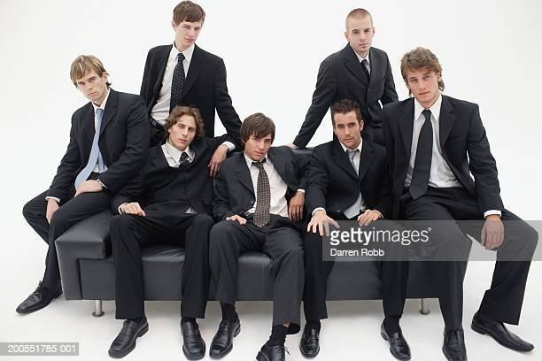 Group of young businessmen sitting on sofa, portrait