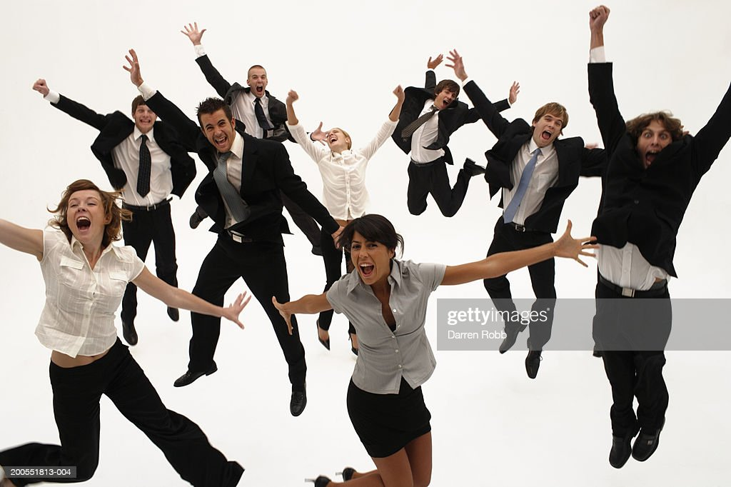 Group of young businesspeople jumping in air with arms out, cheering, elevated view : Stock Photo