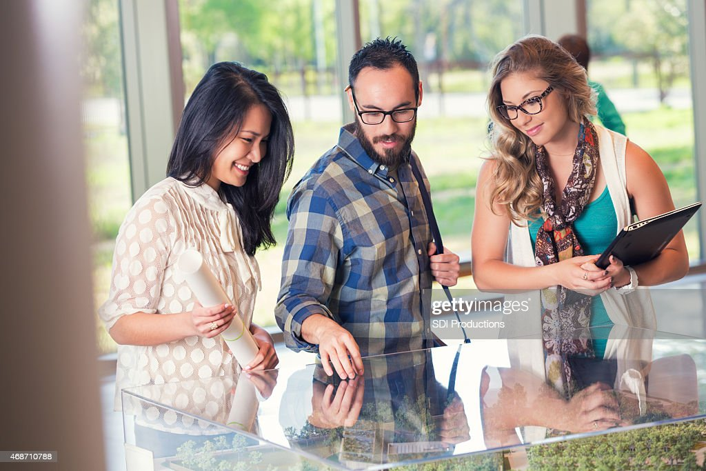 Group Of Young Businesspeople Studying Architecture Model And Blueprints  Together : Stock Photo