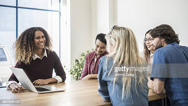 Group of young casual business people at table with laptop