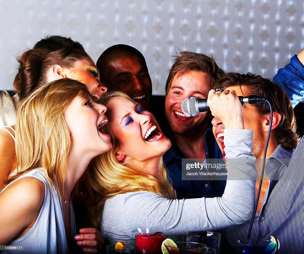 Group of young cheerful people singing