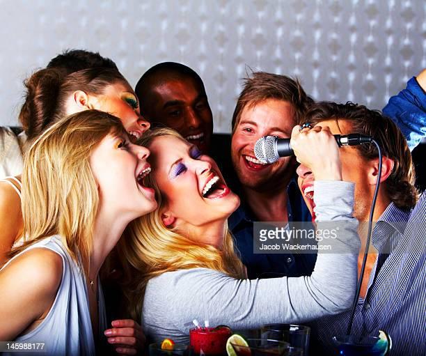 Gruppe von jungen fröhlich Menschen singen
