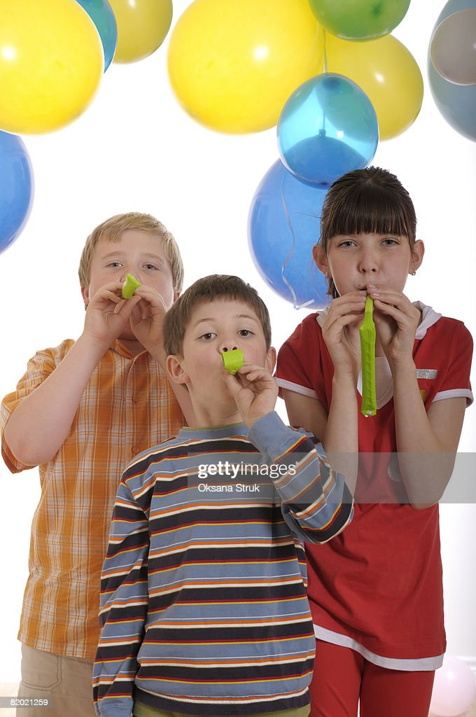 Group of young children blowing party horns : Stock Photo