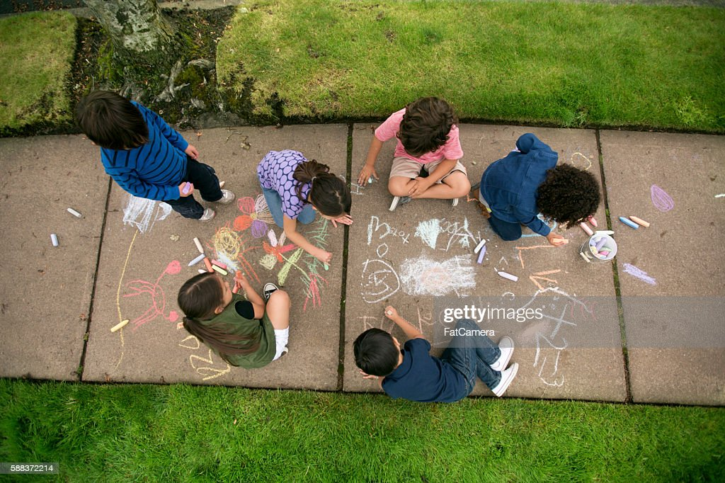Group of young children drawing with chalk on the sidewalk : Photo