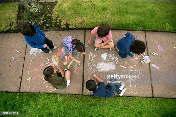 Group of young children drawing with chalk on the sidewalk