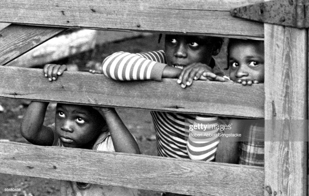 A group of young children lean in and peek through the slats of a wooden fence, somewhere in the Mississippi delta area, TN, 1969.