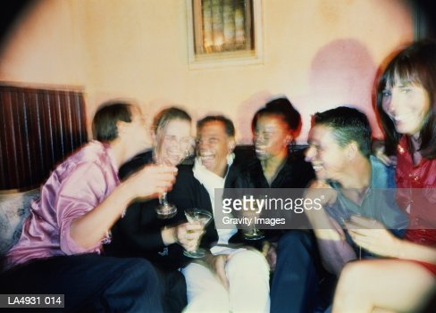 Group of young couples talking and drinking (blurred motion) : Stock Photo