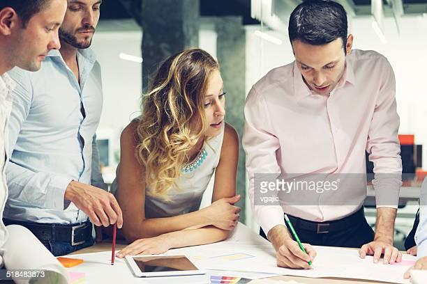 Grupo de jóvenes diseñadores revisar de nuevo proyecto en la oficina.
