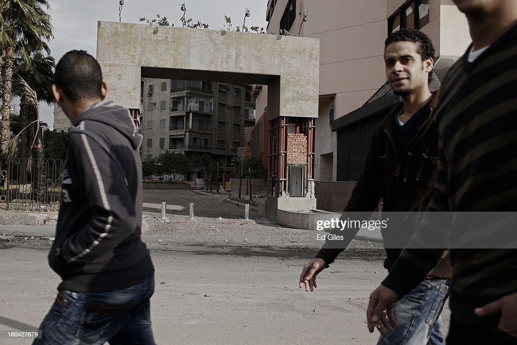 A group of young Egyptian men walk by the driveway to a luxury hotel damaged during earlier clashes between riot police and protesters near Tahrir Square on January 31, 2013 in Cairo, Egypt. Several luxury hotels on the banks of the Nile River in central Cairo were forced to close after being surrounded by violent demonstrations and in one case, being broken into. Protests continued across Egypt nearly one week after the second anniversary of the Egyptian Revolution that overthrew former President Hosni Mubarak on January 25, 2011. Further protests are expected over the coming weekend to commemorate the first anniversary of the Port Said football massacre, when over 70 fans of the Cairo-based Al Ahly football club were killed in a violent post-match brawl between fans of the opposing teams inside the Port Said football stadium after a match between the Al Ahly and Al Masry football teams.