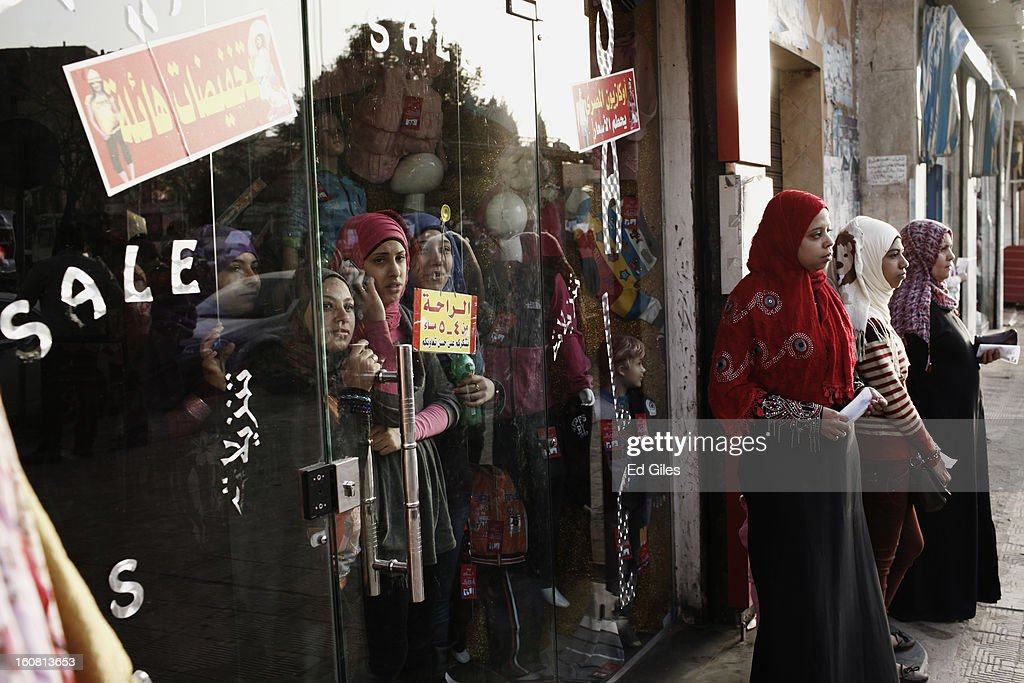 A group of young Egyptian women look through a shop window at a passing march against sexual harassment near the Seiyda Zeinab Mosque, on February 6, 2013 in Cairo, Egypt. Around a thousand Egyptian men and women marched through the Egyptian capital to the city's iconic Tahrir Square on Wednesday to demonstrate against the continuing problem of sexual harassment of Egyptian and foreign women during protests across Egypt. (Photo by Ed Giles/Getty Images).