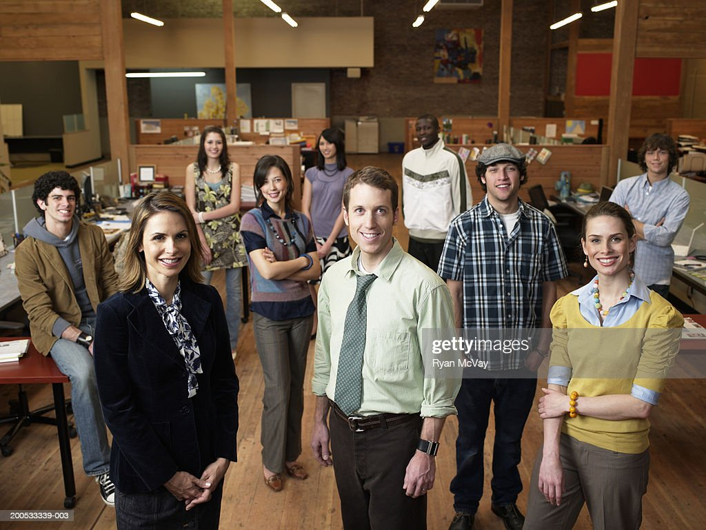 Group of young executives standing in office, smiling, portrait : Stock Photo
