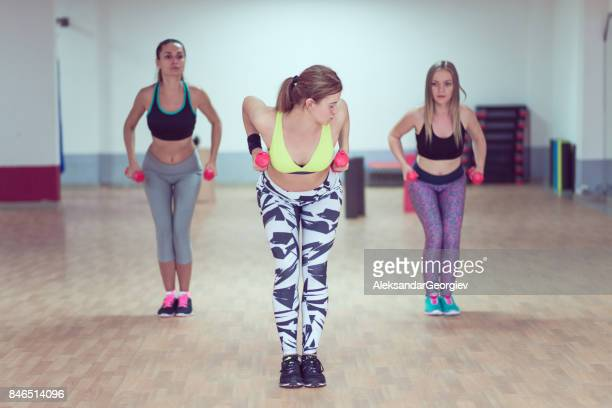 Group of Young Females Doing Squats  With Weights in Gym