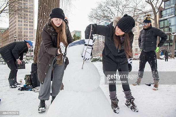 Gruppe junger Freunde eine Schneemann