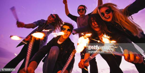 Group of young friends celebrating by holding fireworks at sunset