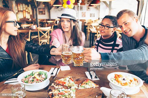 Group of young friends celebrating in restaurant