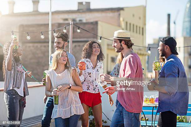 Group of young friends dancing at rooftop party
