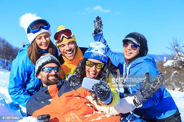 Group of young friends enjoying the snow and making selfie