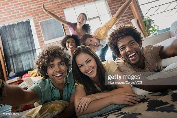 Group of young friends having fun lying on carpet