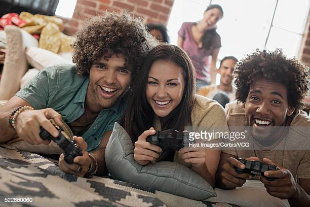Group of young friends having fun playing video games
