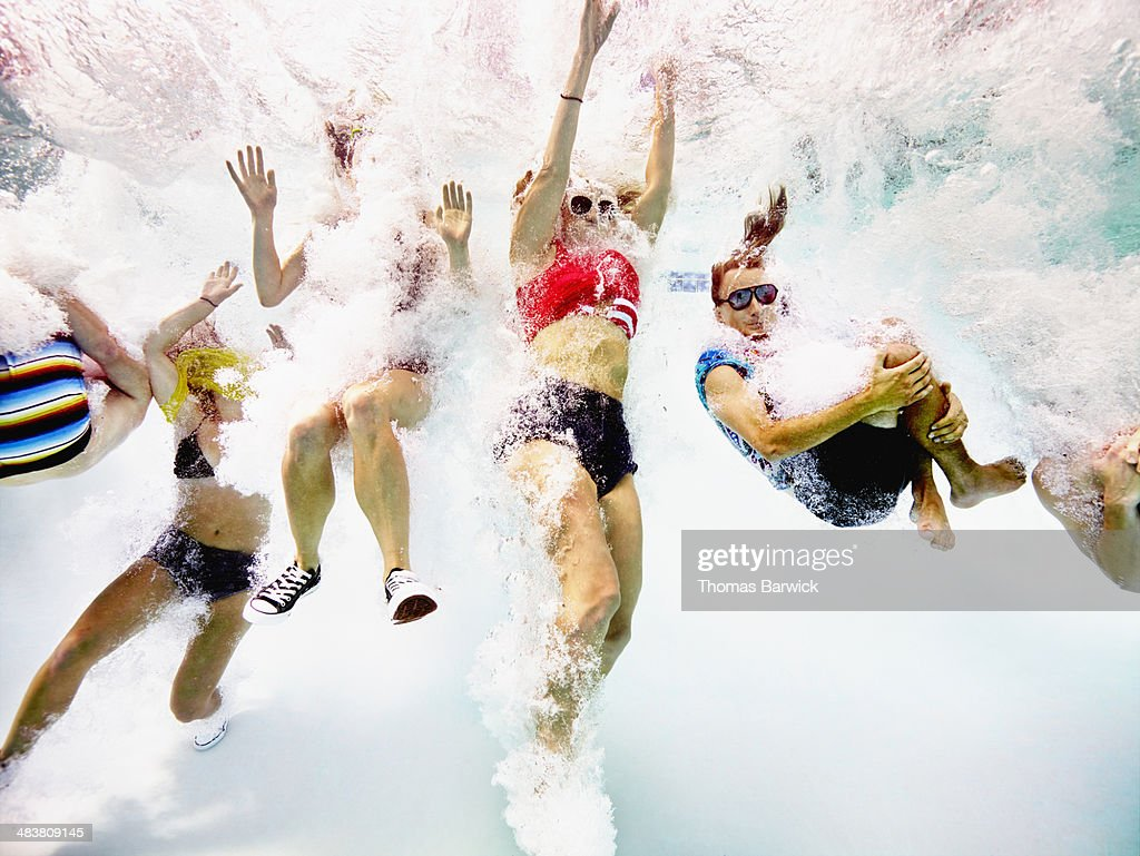 Group of young friends jumping into pool : Stock Photo