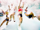 Group of young friends jumping into pool