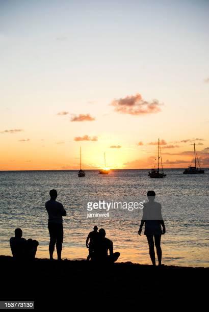 Gruppe von jungen Freunden am Strand bei Sonnenuntergang