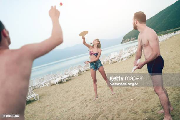 Group Of Young Friends Play Beach Tennis Paddle Ball