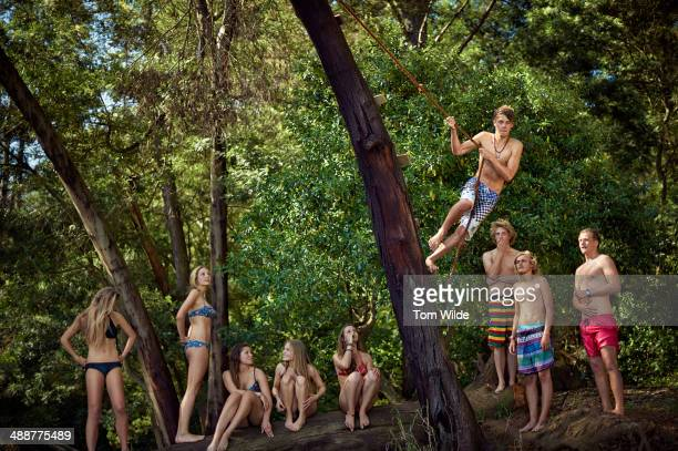 Group of young friends rope swinging