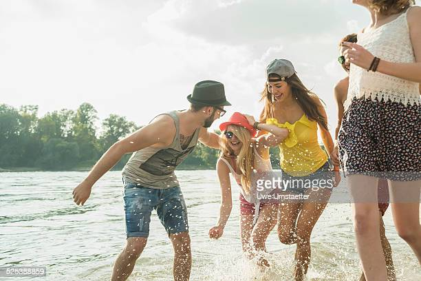 Group of young friends running in lake
