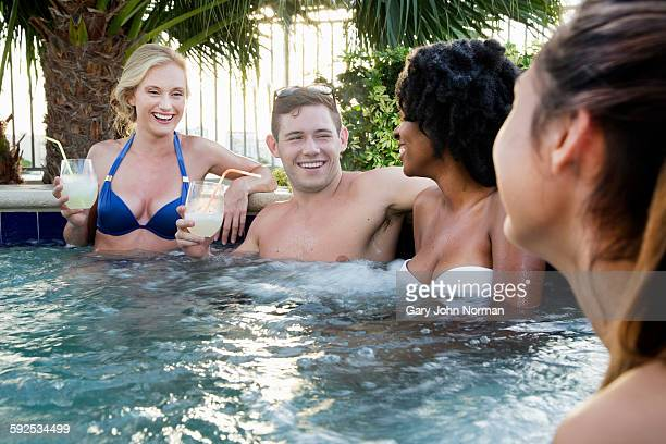 Group of young friends sitting in outdoor spa